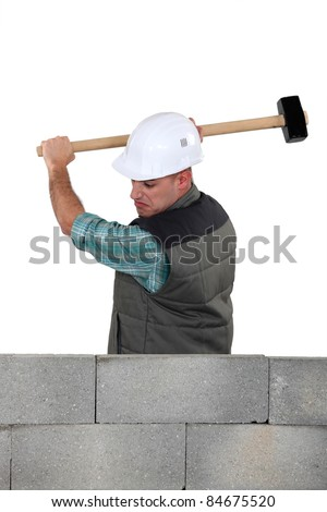 Man hitting a wall with a sledgehammer - stock photo