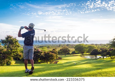 Man hitting golf ball down hill towards ocean and horizon - stock photo