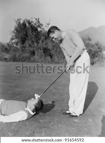 Man hitting golf ball on mans forehead - stock photo