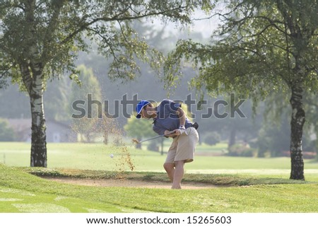 Man hitting golf ball out of sand trap - horizontally framed photo. - stock photo