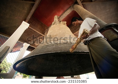 Man hitting is religion the Mingun Bell is one of the world's largest ringing bells. The weight of the bell is 90 tons or199,999 pounds and about 13 feet tall in Sagaing Division , Central of Myanmar - stock photo