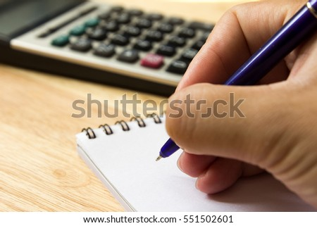 Man hold the pen for note on book with calculator (Concept for financial, business and education)