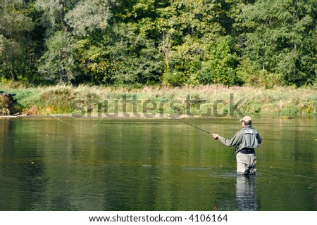 man holdig fishing rod, standing in water - stock photo
