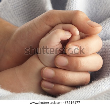 man holding a baby hand, extreme closeup - stock photo