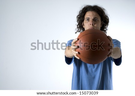 Man holding a basketball out with both hands out in front of him. Horizontally framed photograph. - stock photo