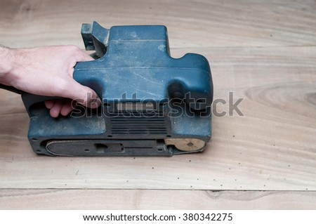 Man holding a belt sander on floor or table sanding surface - stock photo