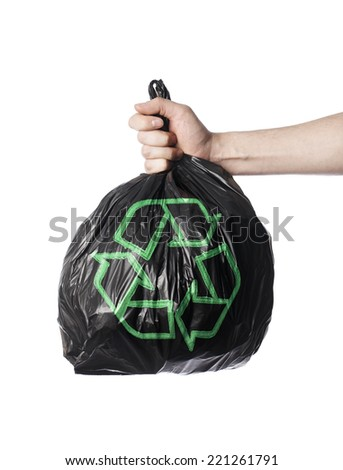 Man holding a black trash back with green Recycling symbol. - stock photo