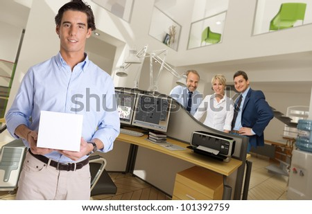 Man holding a blank box in a modern office - stock photo