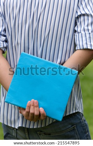 Man holding a blue textbook - stock photo