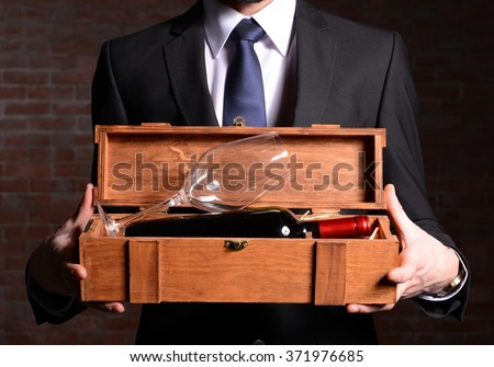 Man holding a bottle of red wine and glass in wooden box on brick wall background - stock photo
