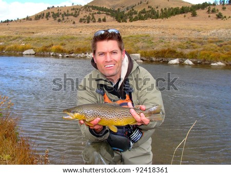 """Man holding a brown trout caught fly fishing on a meandering meadow stream, South Platte or """"Dream Stream"""", Colorado - stock photo"""