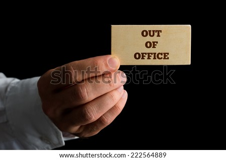 Man holding a business card reading - Out of Office - indicating that he and his services are unavailable due to absence. - stock photo