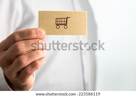 Man holding a business card with a shopping icon of a line drawn shopping cart over his white shirt with copyspace, close up of his hand.
