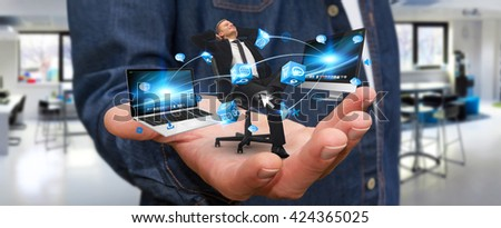 Man holding a businessman in his hand connected to modern devices '3D rendering'