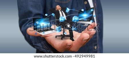 Man holding a businessman in his hand connected to modern devices 3D rendering