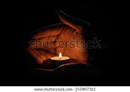 Man holding a candle in the dark - stock photo