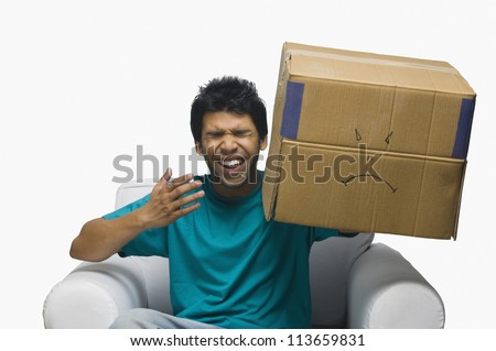 Man holding a cardboard box with a smiley face and laughing - stock photo