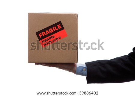 Man holding a cardboard moving box with a orange fragile sticker on a white background