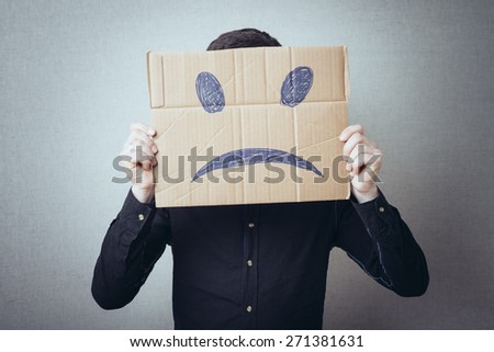 man holding a cardboard with a sad smiley - stock photo