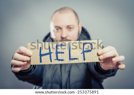 man holding a cardboard with the text Help - stock photo