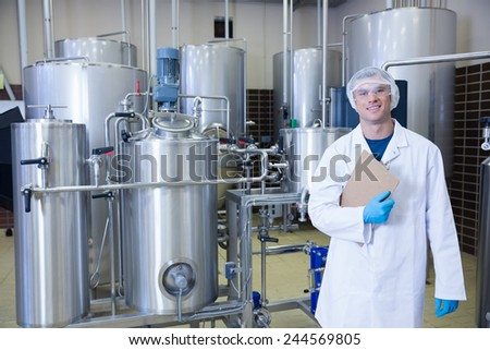 Man holding a clipboard standing in front of the container in the factory