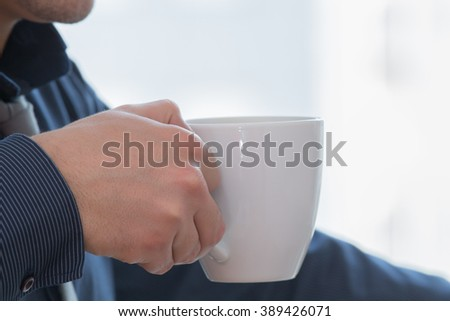 Man holding a coffee cup.