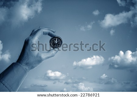 Man holding a compass over clear sky - stock photo