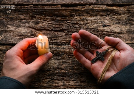 man holding a cross and a candle - stock photo