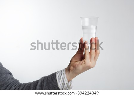 Man holding a disposable plastic cup with water. The lack of drinking water. Water for proper nutrition