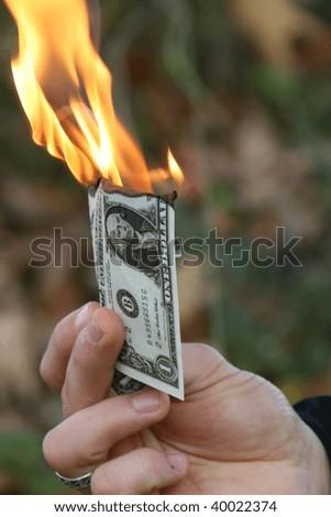 Man holding a dollar bill burning - stock photo
