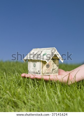 Man holding a dollar house outside