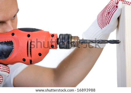 Man holding a drill on a peace of wood plank - stock photo
