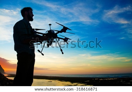 man holding a drone for aerial photography. silhouette against the sunset sky - stock photo