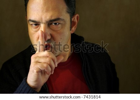 Man holding a finger on his mouth demanding silence. - stock photo