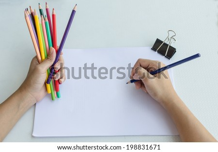 Man holding a fistful of colored pencils in one hand while commencing sketching in a sketch book to show off his creativity and artistic skills with the other, view from above - stock photo