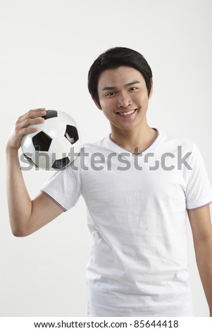 man holding a football at the shoulder - stock photo