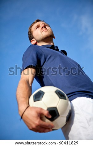 Man holding a football outdoors with the sky on the background - stock photo