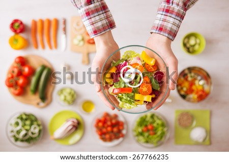 Man holding a fresh garden salad bowl with raw sliced vegetables, hands close up top view, ingredients and utensils on background - stock photo