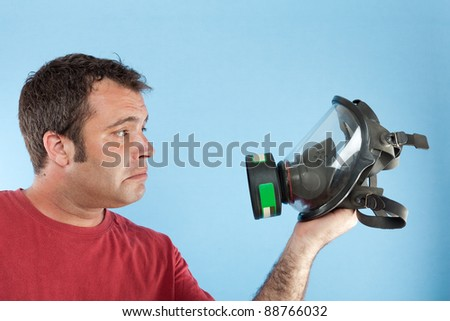 Man holding a gas mask while looks it with sad face