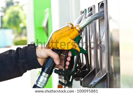 Man holding a gasoline nozzle in his hand - stock photo