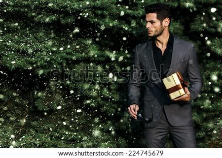 Man holding a gift near the Christmas tree - stock photo