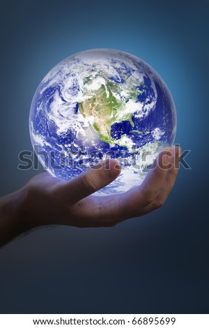 Man holding a glowing earth in his hand. Earth image provided by NASA. - stock photo