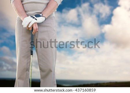 Man holding a golf club against blue sky with white clouds - stock photo
