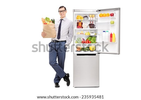 Man holding a grocery bag and leaning on a fridge isolated on white background - stock photo