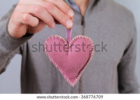 Man holding a heart shape close up. Love, valentine concept