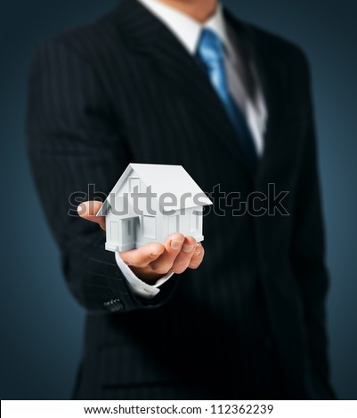 Man holding a house in hand - stock photo