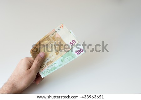 Man holding a hundred and fifty  Euro banknote in his hands - stock photo