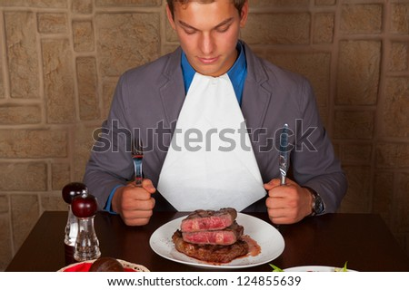 man holding a knife and a fork ready to eat a beef steak - stock photo