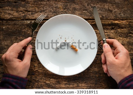 man holding a knife and fork next to a white plate with a cigarette - stock photo
