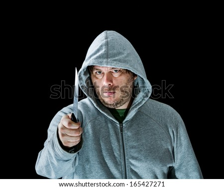 Man holding a knife as a threat to someone on the other side. - stock photo